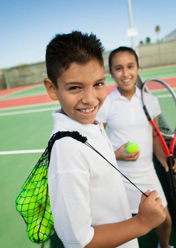 children carrying their tennis equipment